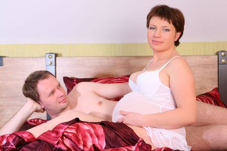 Young future parents is lying on the bed