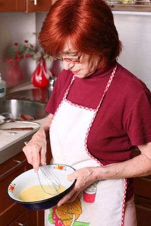 Grandmother beats eggs in a bowl