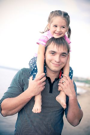 little girl barefoot: Outdoor portrait of young father with a daughter on his shoulders