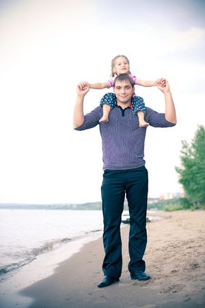Young father walking dawn the river bank with his daughter sitting on his shoulders photo