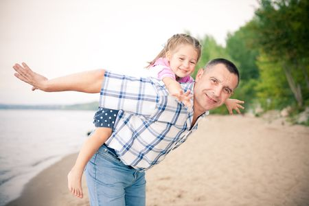 Outdoor portrait of middle-aged smiling man and his granddaughter