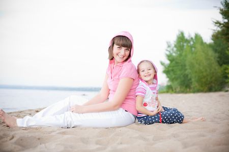 Outdoor portrait of happy mother and her daughter sitting on the beach photo