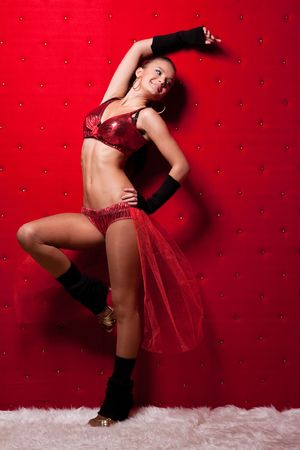 Attractive woman in sexy clothes near the red wall photo