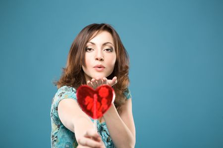 Attractive woman holds a heart lollipop and blows kisses to somebody over blue background  Stock Photo - 6637116