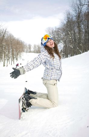 Happy snowboarder with a grin  is sitting on the snow