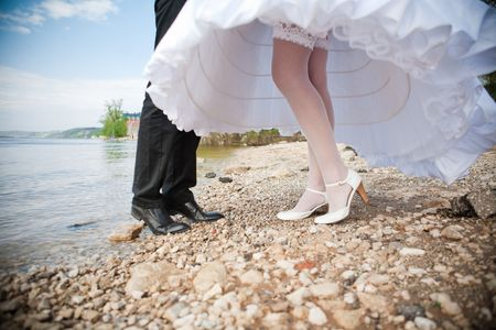 Groom and bride is walking on the bank of river