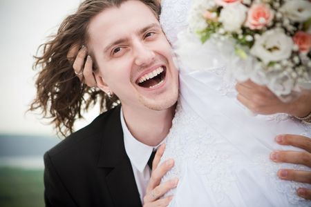 arm bouquet: Happy groom is embracing the bride outdoors Stock Photo