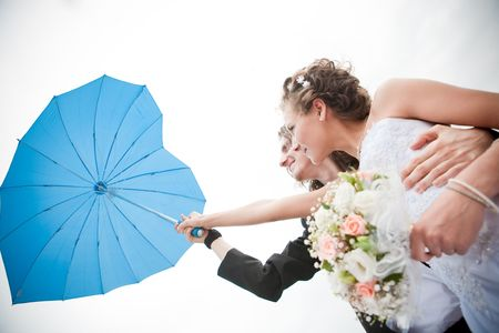Happy groom and bride is holding an umbrella Stock Photo