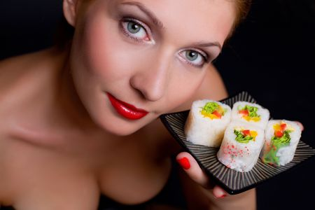 Pretty woman is holding a plate with japanese food over black background
