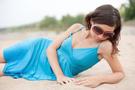 Attractive young woman is lying on the beach. photo