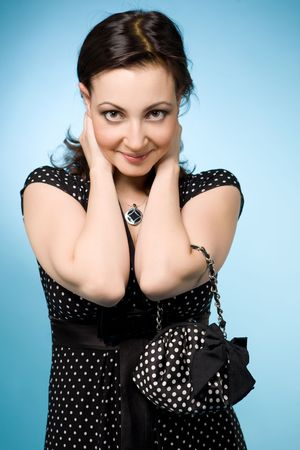 Portrait of a happy Jewish woman with a grin in retro black dress. She holds a small black dolly-bag. Over blue background Stock Photo