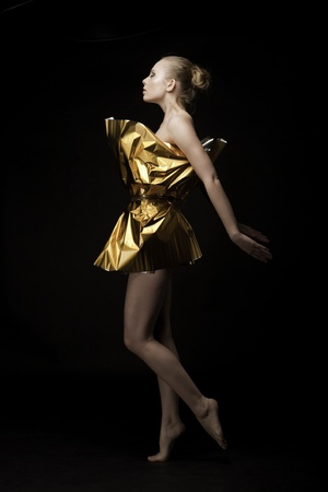Attractive dancer in gift wrapping standing over black background. photo