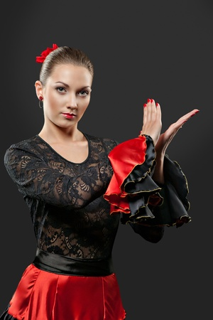 Young spanish flamenco dancer in full action over black background Stock Photo