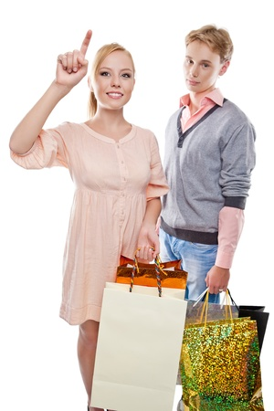 Happy woman and tired man is holding paper bags over white background photo