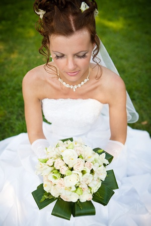 Attractive bride is sitting with bunch of flowers on the lawn Stock Photo