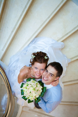 Happy bride and groom is standing on the stairs photo