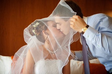 Newlywed couple kissing each other in the bedroom photo