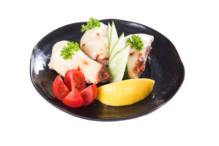 Chicken pieces with slices of tomato, cucumber and lemon isolated over a white background photo