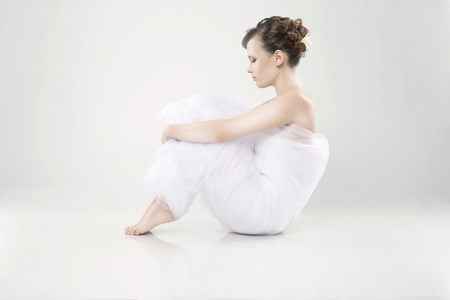 Attractive young woman wrapped in fabric sitting on the floor photo