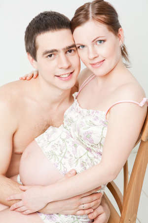 Young pregnant woman sitting on the chair with her husband photo