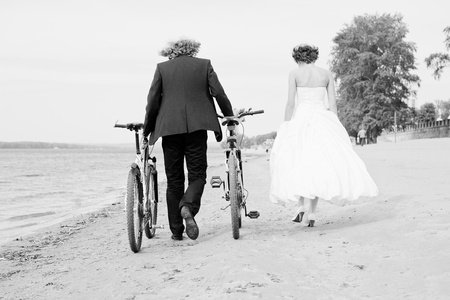 B W photo of groom and bride, which walks on the beach with bicycles photo