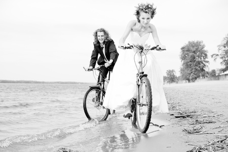 B W photo of Happy bride and groom rides on bicycles photo