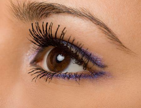 female wide open brown eye with long eyelashes macro photo