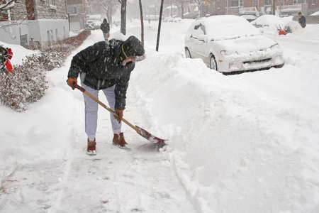 montreal: Woman shoveling after a snow storm. Canada.