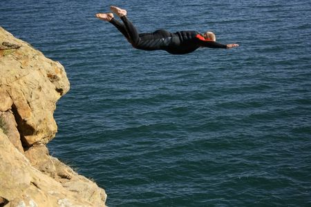 no rush: A man jumping off a cliff in a wetsuit into a dam. Stock Photo