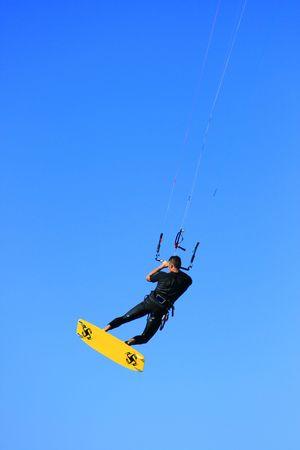 kiter: A kitesurfer in midair on blue background