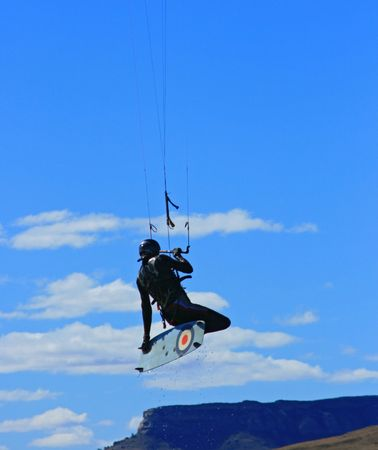 kiter: A kiter jumping and doing a grab with mountain range below and blue sky and clouds as background