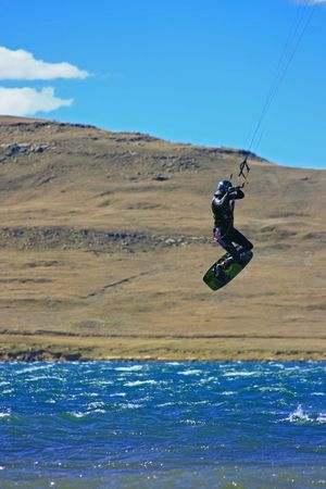 kiter: A kiter jumping to right side of page with scenic mountains and sky
