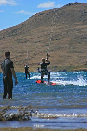 kite surfing: Een kite surfer kijkt 3 andere kitesurfers in het water kitesurfen. Al met wetsuits met schilderachtige bergen achter