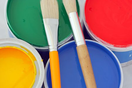 descriptive: Vertical picture of paints in red,blue,green and yellow on white and 2 brushes
