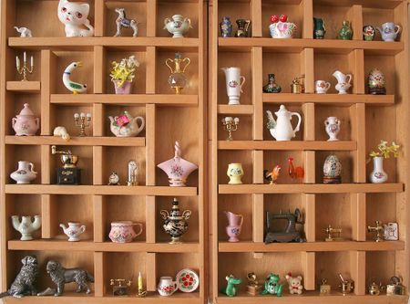 miniatures: A collection of miniatures and knick-knacks in a wooden display Stock Photo