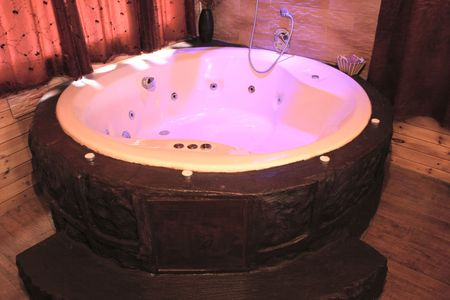 hot tub: A softly lit jacuzzi hot tub in a romantic wood cabin Stock Photo