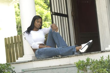woe: Beautiful African American model sitting on porch of older home in urban setting