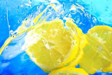 Slice of lemon splashing in water.