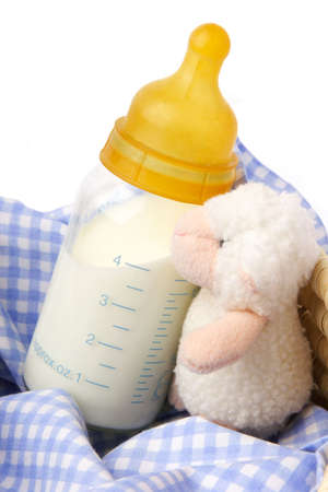 Open  milk bottle with measure and  soft toy sheep. Stock Photo