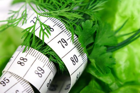 Green diet. Vegetables: lettuce, leaves, dill and chives with tape-measure. Stock Photo