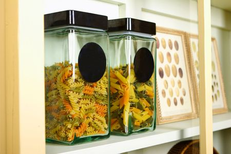 Glass jares of pasta in a kitchen cupboard.