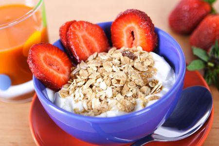 Healthy breakfast: musli with yoghurt and fresh strawberries. Cup of carrot juice is good breakfast drink.