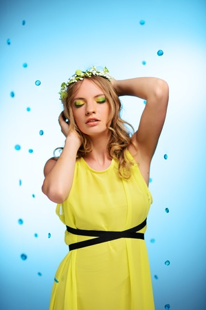 Girl in yellow dress with may-lily chaplet on blue background  photo