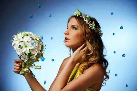 Girl in yellow dress with may-lily chaplet and bouquet on blue background  photo