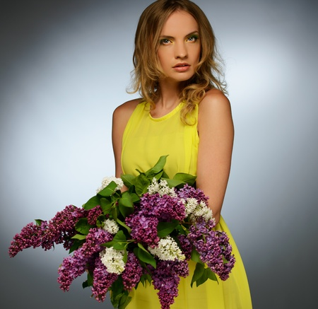 Young beautiful girl in yellow dress holding lilac bouquet  photo