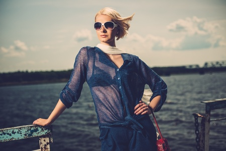 Stylish beautiful blond woman wearing white scarf and sunglasses  standing near rails of old pier photo