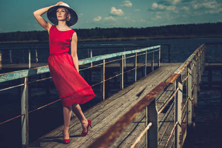 Stylish woman in white hat and red dress standing on old wooden pier  photo