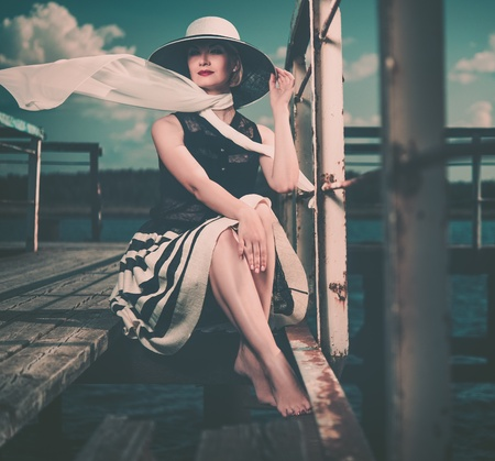 clothes rail: Beautiful woman wearing hat and white scarf sitting on old wooden pier  Stock Photo