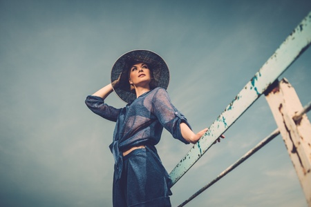 Stylish woman in white hat standing near rails of old pier photo
