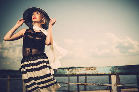 fashion dresses: Woman in white hat and scarf standing near old pier rails